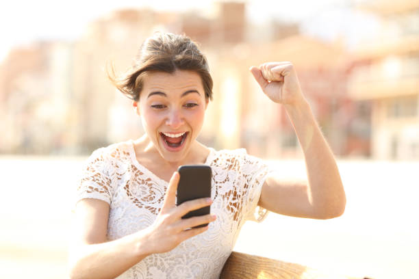 Excited woman reading amazing news on a phone Excited woman reading amazing news on a phone refund stock pictures, royalty-free photos & images