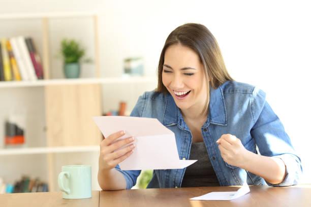 mulher excitada lendo boas notícias em uma carta - happy test results - fotografias e filmes do acervo