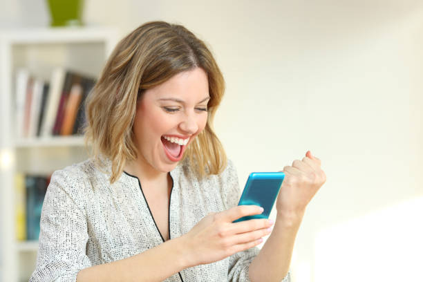 Excited woman reading smart phone content Excited woman reading online smart phone content at home lottery stock pictures, royalty-free photos & images