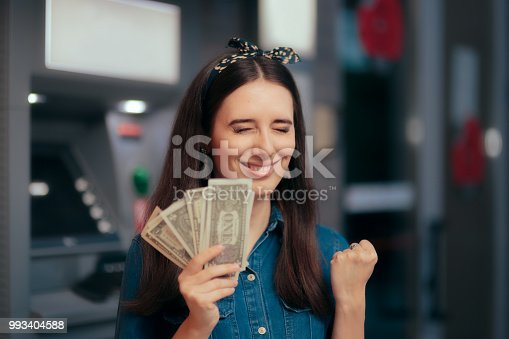 istock Excited Woman Receiving Salary at ATM Teller Machine 993404588
