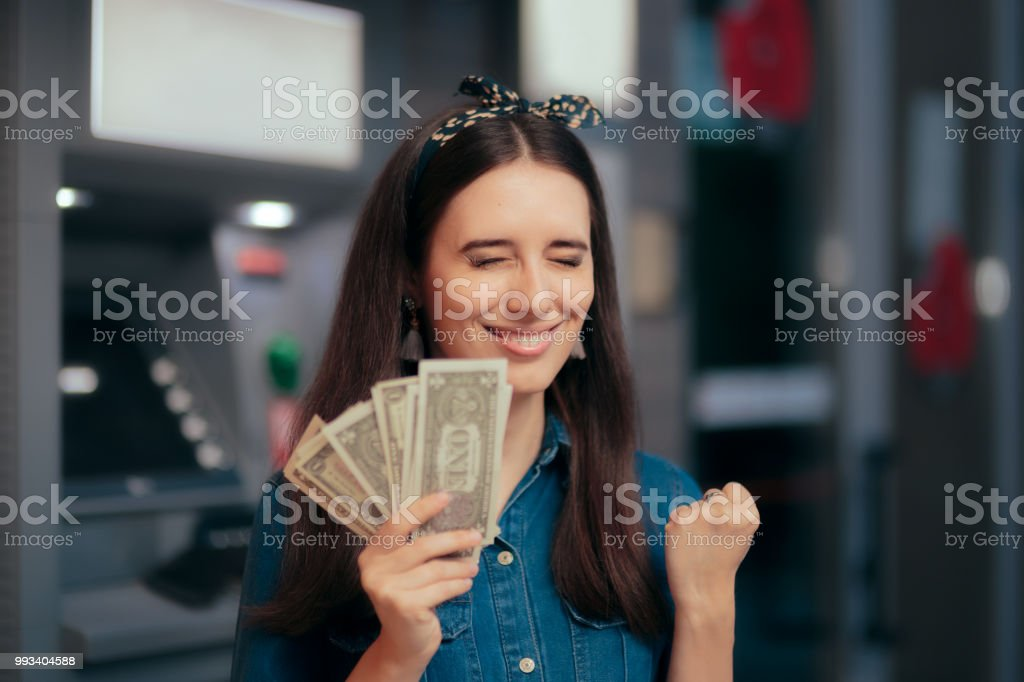 Excited Woman Receiving Salary at ATM Teller Machine stock photo