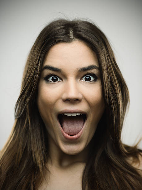 Excited woman screaming against gray background - Photo