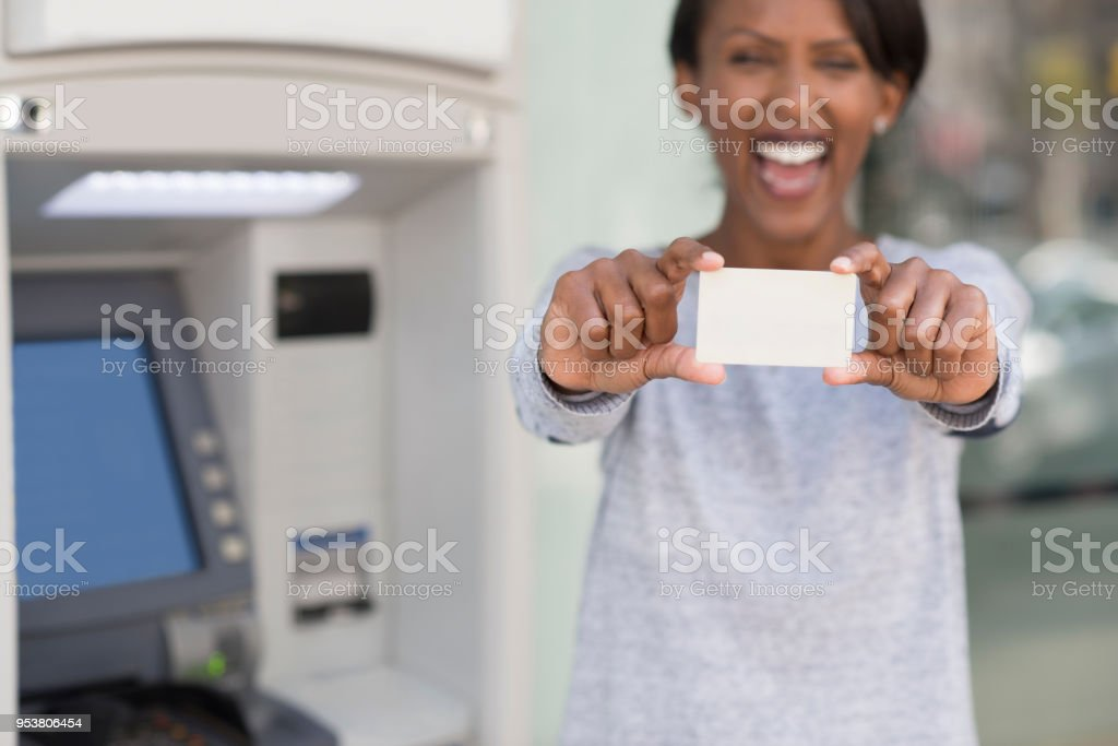 Excited woman showing credit / debit card. The customer satisfied with bank ATM service. stock photo