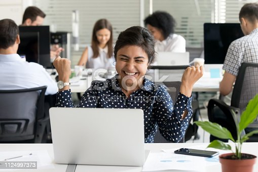 Surprised indian worker sitting at desk in coworking space with colleagues looking at notebook screen feels excited and amazed. Female received unexpected great opportunity promotion or getting reward