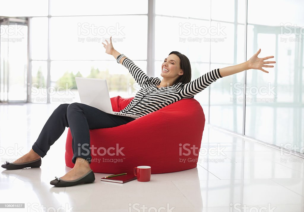 Excited woman sitting on a bean bag with laptop and arms outstretched royalty-free stock photo