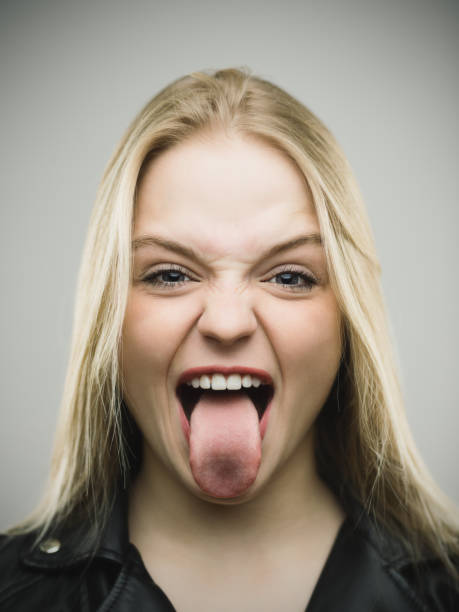 excited woman sticking out tongue against gray background - sticking out tongue stock photos and pictures