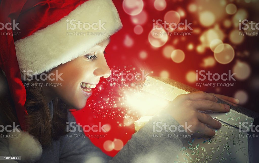 Excited woman wearing Santa hat opening a magic box royalty-free stock photo