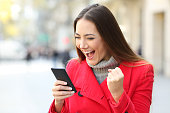 istock Excited woman winning on line on the street in winter 892038760
