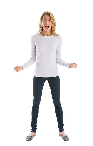 Excited Woman With Clenched Fists Shouting Portrait of excited young woman with clenched fists shouting while standing against white background long sleeved stock pictures, royalty-free photos & images