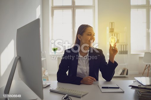 Happy smart businesswoman holding burning light bulb having brilliant idea while working in office