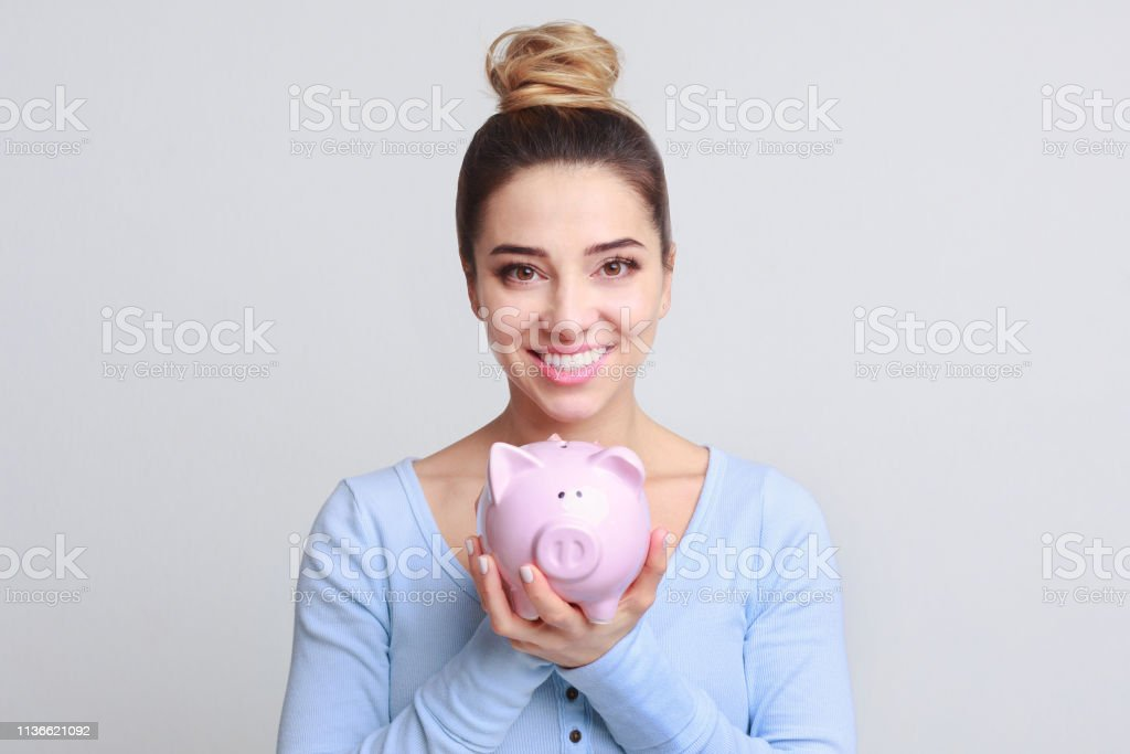 Excited woman with piggy bank on background stock photo