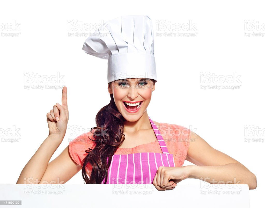 Excited woman with whiteboard Portrait of happy young woman wearing chef's hat and an apron, holding a whiteboard and pointing with index finger, smiling at the camera. Studio shot, isolated on white. 20-24 Years Stock Photo