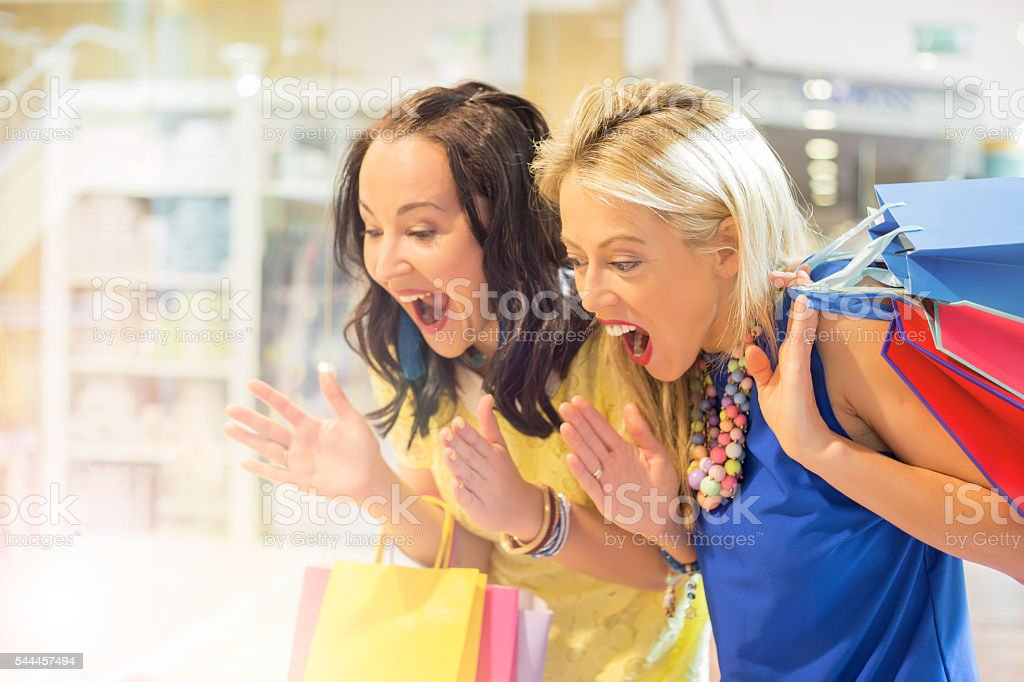 Excited women at the shopping mall window-shopping stock photo