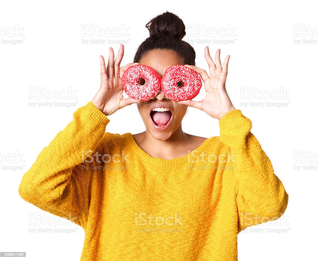 Excited young african woman covering her eyes with donuts stock photo