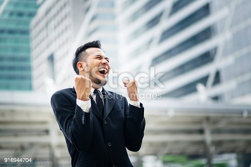 istock Excited young asian businessman happy and hurray while standing outdoors with office building in the background 916944704