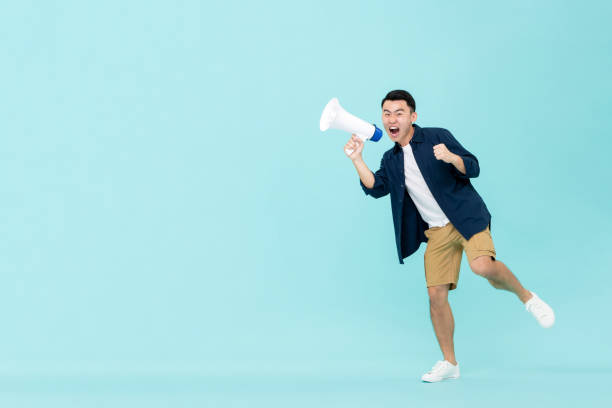 Excited young Asian man holding megaphone and shouting stock photo