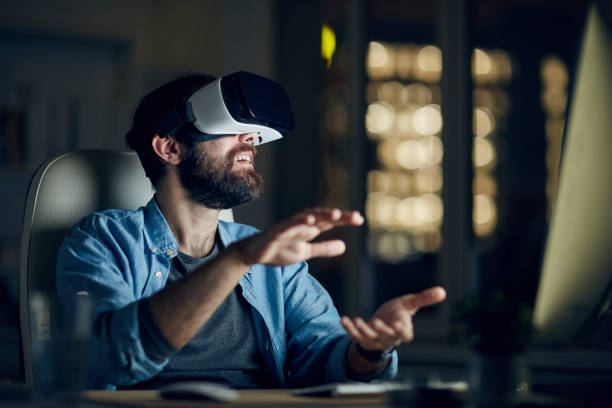 Excited young bearded man sitting in front of computer and gesturing hands while testing new app via VR device stock photo
