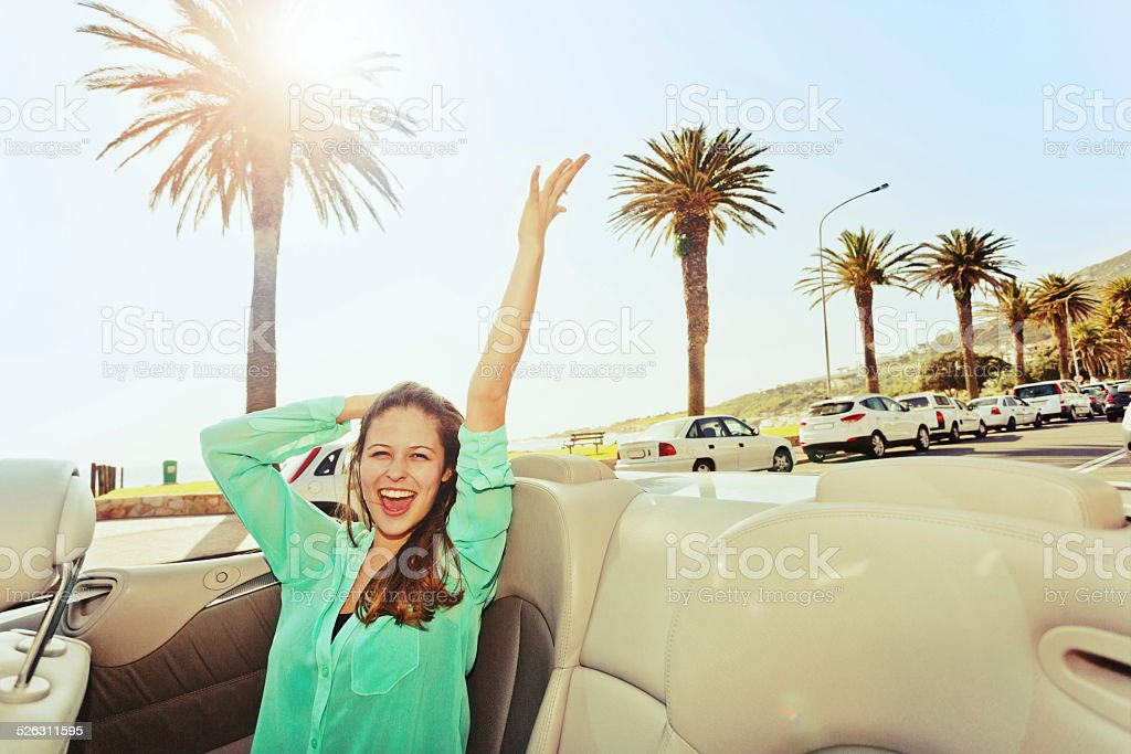Excited young beauty rides in convertible along palm-lined promenade stock photo