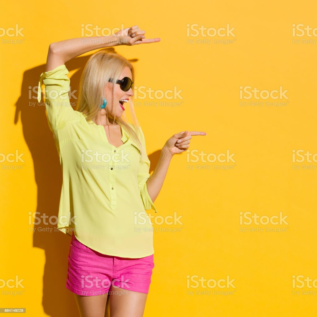 Excited Young Blond Woman Is Shouting, Pointing And Looking Away stock photo