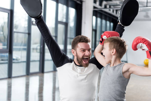 Excited young boy boxer with his coach at training stock photo