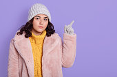 Excited young brunette woman in pale pink fur coat posing isolated over lilac background, serious scared lady pointing index fingers aside, copy space for advertisement.
