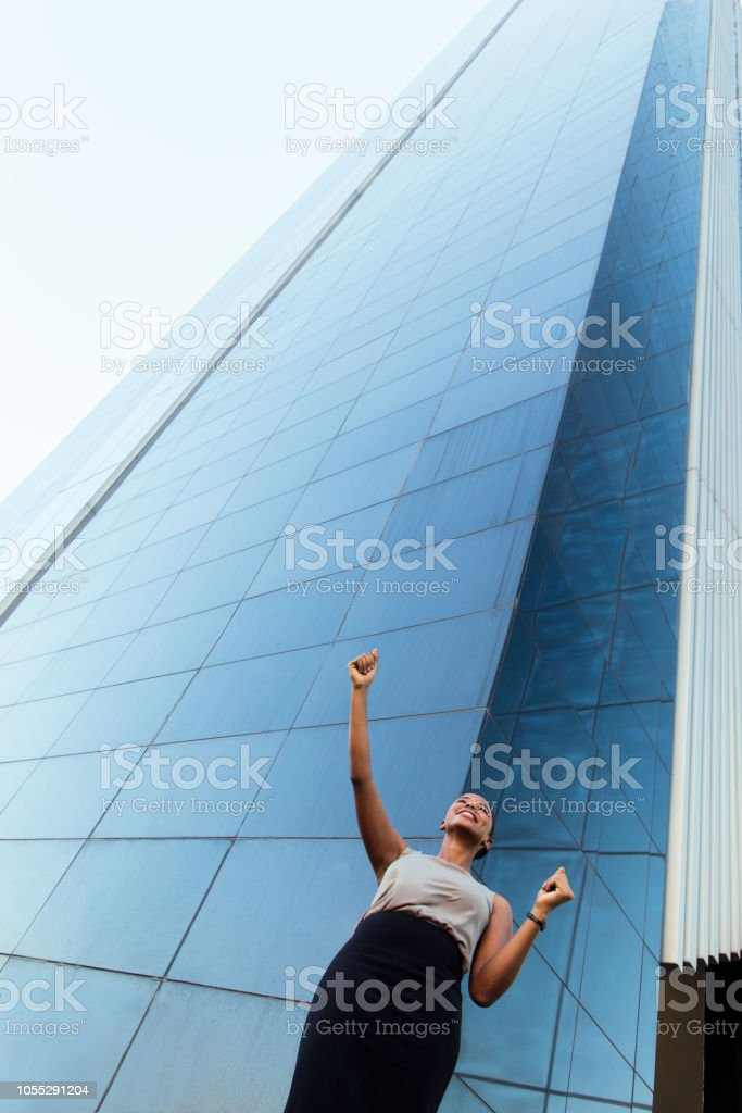 Excited young business woman raising hands stock photo