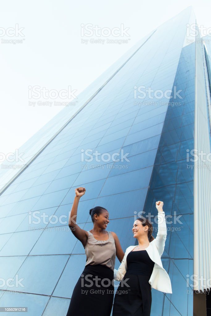 Excited young business women raising their hands outside stock photo