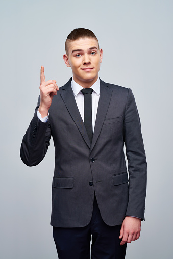 Excited Young Businessman Holding Finger Up Stock Photo ...