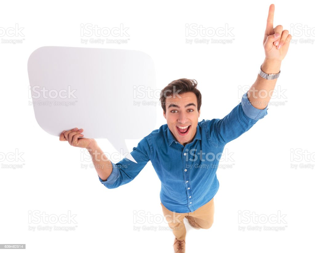 excited young casual man holding speech bubble is pointing up stock photo