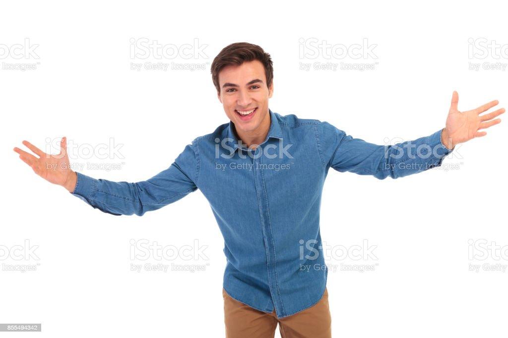 begeistert junge legerer Mann einladend – Foto