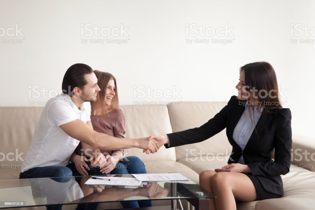 Excited young couple and real estate agent handshaking, successful deal stock photo