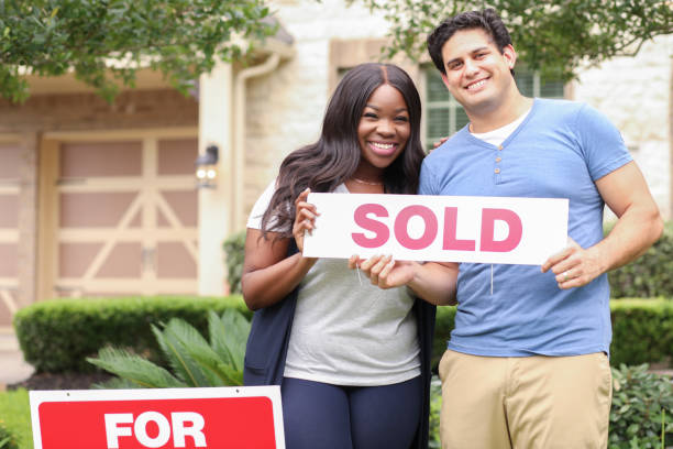 Excited young couple buys their first home. stock photo