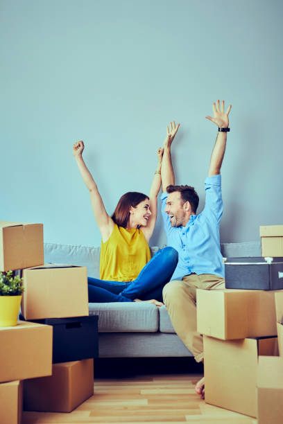 Excited young couple moving in stock photo