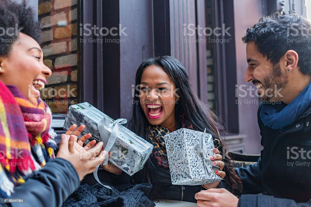 Excited Young Friends Exchanging Christmas Gifts stock photo