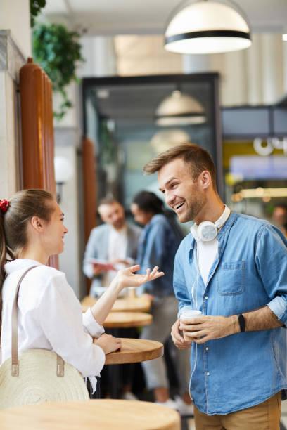 Aufgeregte junge Freunde in lässigen Outfits stehen in modernen Café und Trinken Kaffee, während die letzten Nachrichten zu diskutieren – Foto