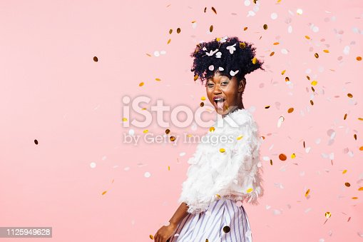 istock Excited young girl having fun throwing confetti 1125949628