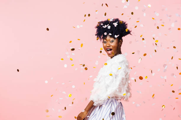 excited young girl having fun throwing confetti - carlos david stock pictures, royalty-free photos & images
