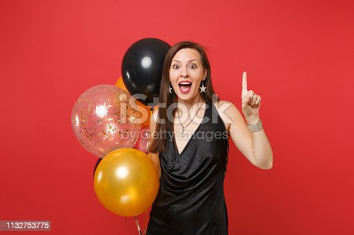 istock Excited young girl in black dress celebrating pointing index finger up holding air balloons isolated on red background. International Women's Day Happy New Year, birthday mockup holiday party concept. 1132753775
