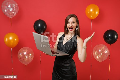 istock Excited young girl in little black dress spreading hands, working on laptop pc computer while celebrating on bright red background air balloons. Happy New Year, birthday mockup holiday party concept. 1132756686
