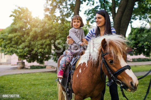 Girl enjoying pony ride, mother watching her