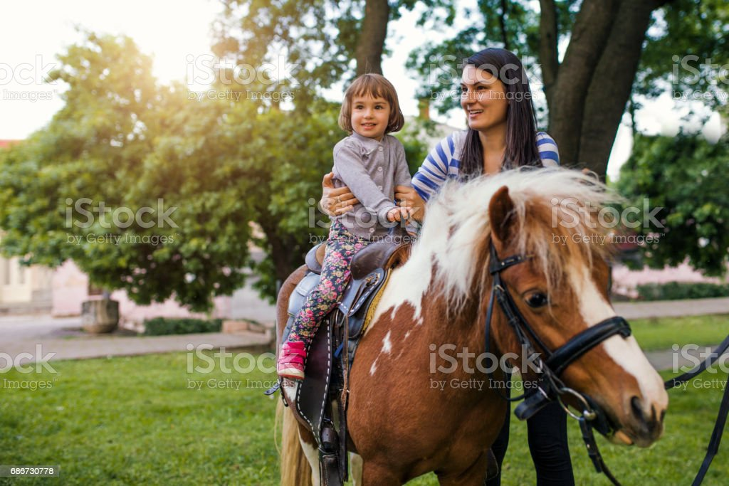Excited Young Girl Taking a Pony Ride stock photo