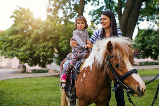 Excited Young Girl Taking a Pony Ride Girl enjoying pony ride, mother watching her pony stock pictures, royalty-free photos & images