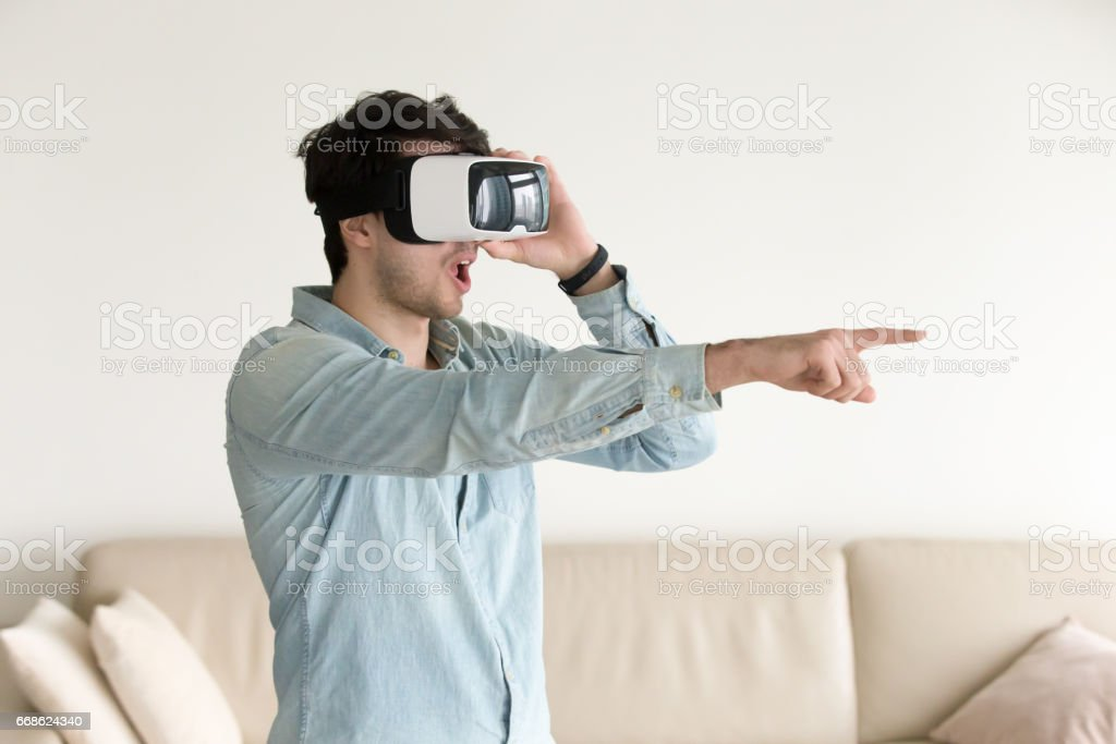 8e690941f6db Excited young guy experiencing virtual reality wearing VR headset indoors -  Stock image .