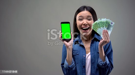 istock Excited young lady holding smartphone and euro banknotes, online lottery winner 1144431848