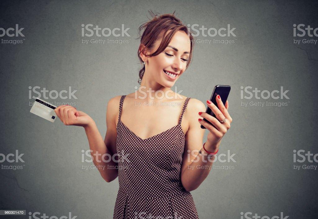 demoiselle excitée avec GSM détenant la carte de crédit - Photo
