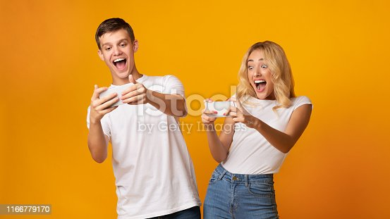 istock Excited young man and woman playing together on smartphones 1166779170