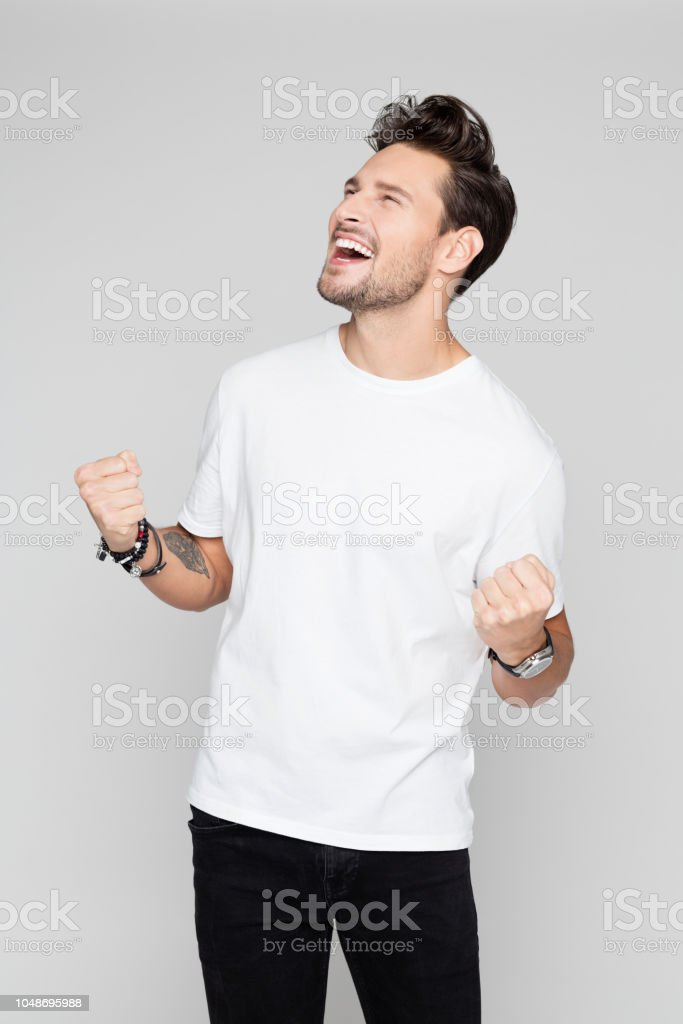 Excited young man celebrating success Portrait of excited young man celebrating success and punching air on grey background 25-29 Years Stock Photo