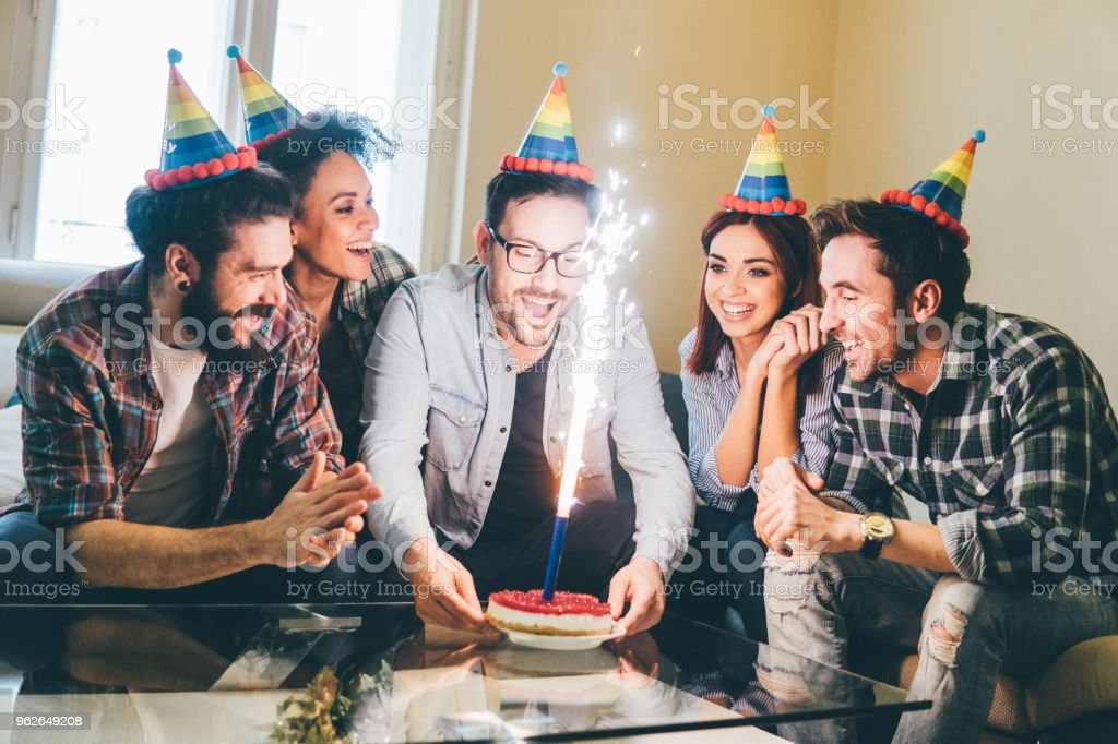 Young people having birthday cake at home