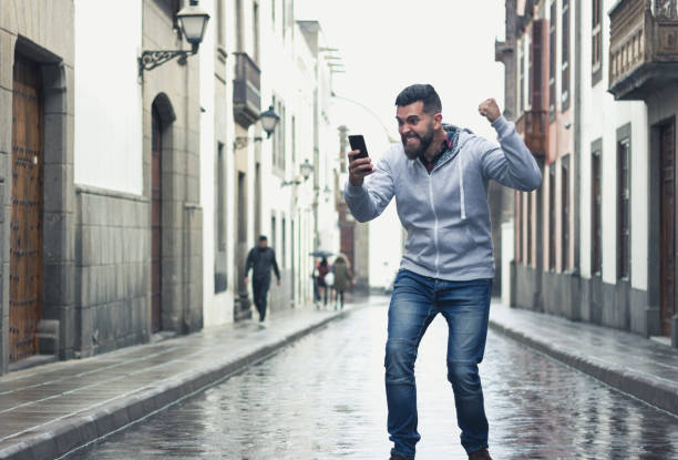 Excited young man looking at cellphone with victorious expression in the middle of the street stock photo