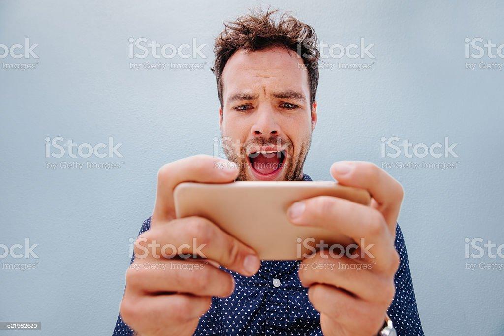 Eccitato giovane uomo guarda verso un telefono cellulare - Foto stock royalty-free di Abbigliamento casual